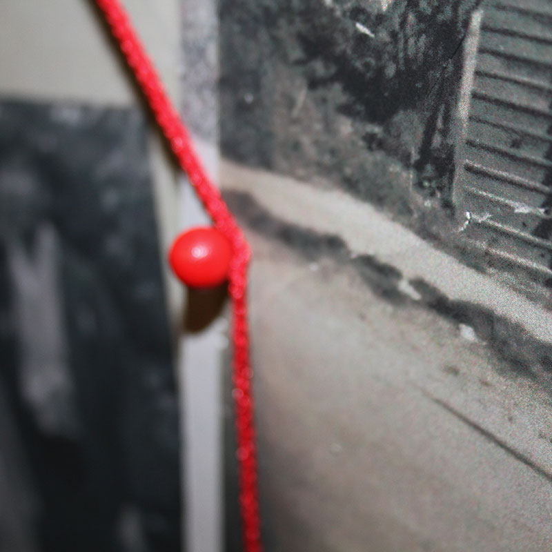 An old, gray photo is pinned to a wall by a bright red pin. There is a bright red string that is wrapped around the pin that leads out of the picture.